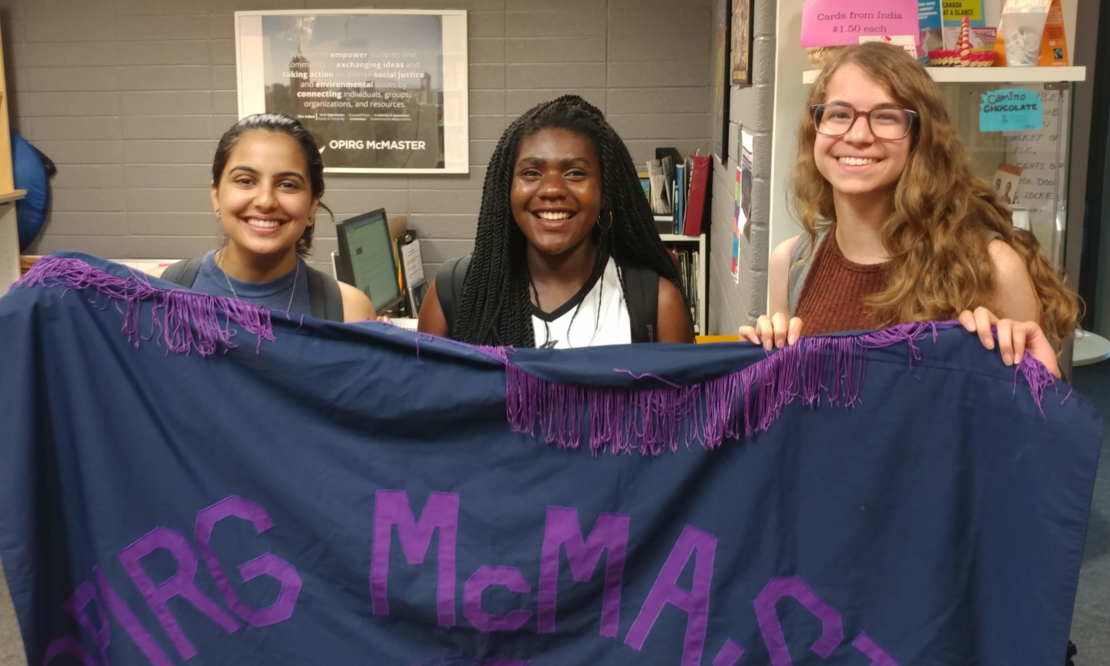 """Three students smiling and holding a purple and blue banner with """"OPIRG McMaster"""" on it."""