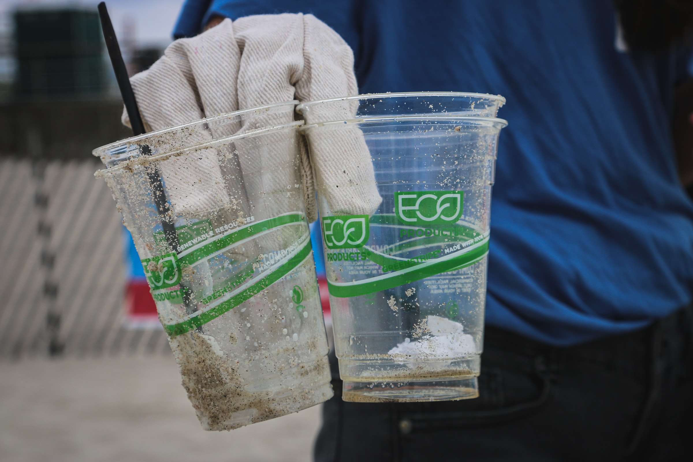 compostable cups still litter, held in gloved hand